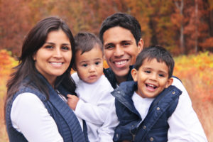 family of four smiling and hugging