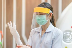 A dental professional wearing PPE also worn by your Love Field dentist