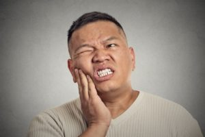 Pained man hand on cheek should see Far North Dallas dentist