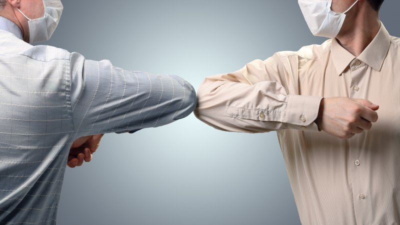 Two men greeting each other using elbow bump