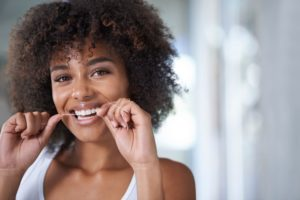 young woman flossing to maintain healthy gums
