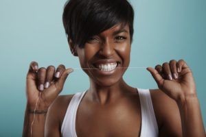 Woman flossing as recommended by her Mesquite dentist