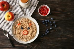 Bowl of oatmeal with a face made of berries. The bowl is surrounded by apples, blueberries, and diced strawberries.