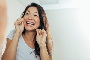 woman flossing in mirror every day