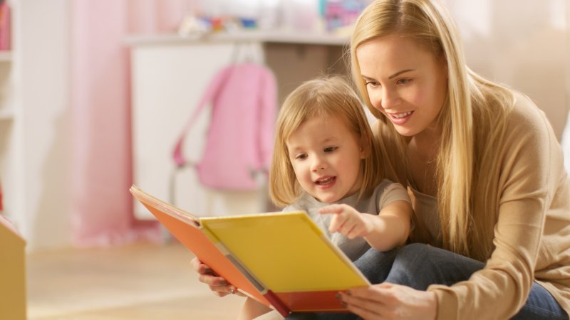 Mother and child reading book together