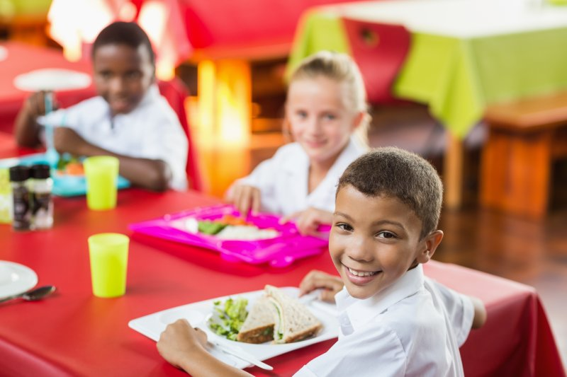 child smiling during school lunch